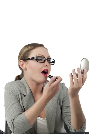 Close-up image of businesswoman applying red lipstick while looking at the mirror Stock Photo - 17521032