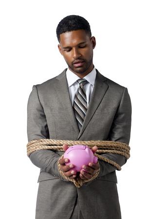 aieron: Business crisis concept represented by a tied businessman holding a piggy bank