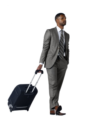 Portrait of confident businessman with luggage walking on a white surface Stock Photo - 17519902