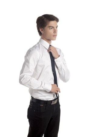 Portrait of a handsome guy holding his tie looking away on a white surface Stock Photo - 17519641
