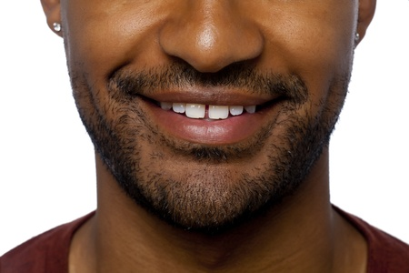 aieron: Cropped image of man face focusing the lips and nose smiling on a white surface