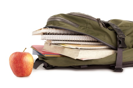 educational tools: Close-up image of a loaded backpack and apple against the white surface