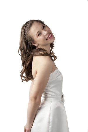 Side view image of a lovely lady on prom dress smiling on a white surface photo