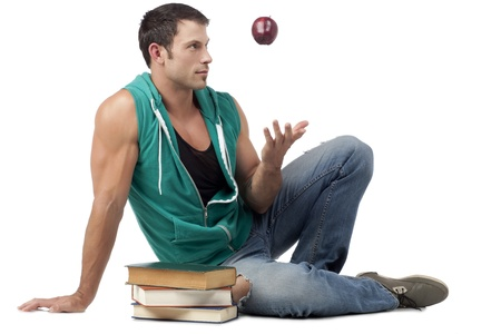sleeveless hoodie: Image of a muscular man throwing an apple while sitting beside the books on a white background Stock Photo