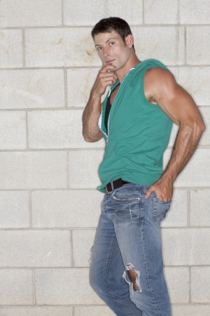 sleeveless hoodie: Portrait of a man wearing sleeveless hooded vest and showing his muscular biceps while leaning on the wall