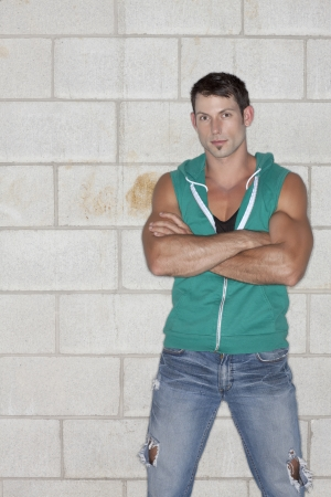 sleeveless hoodie: Portrait of muscular man with crossed arm while standing against the wall background
