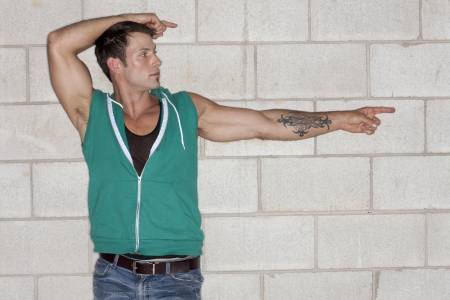 sleeveless hoodie: Portrait of muscular man with tattoo pointing to the side of a wall background Stock Photo