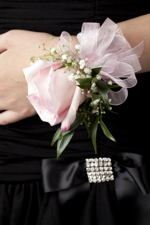 Close-up image of a pink rose corsage on the woman's wrist