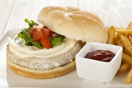 Close-up image of plate with chicken hamburgers and potato fries isolated on a wooden table photo