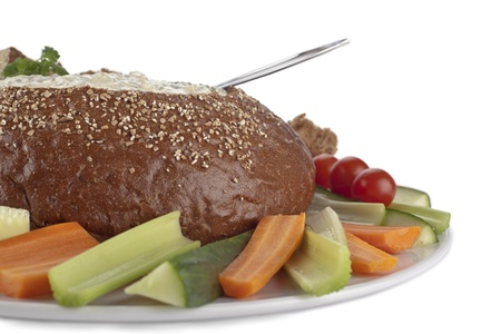 pumpernickel: Close up image of pumpernickel bread filled by spinach dip with slices of vegetables against white background