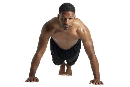 aieron: Colpo facciata di uomo nero facendo push up esercizio su uno sfondo bianco