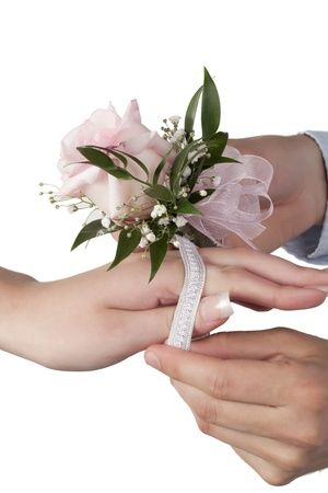 Close-up image of hand putting pink rose corsage on the females wrist