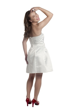 Rear view of teenager in white prom dress smiling on a white surface Stock Photo - 17519365