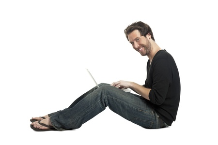Side view image of a happy man using his laptop while sitting on a white surface Stock Photo - 17519638