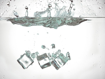 submerging: Ice cubes dropped in to the water slowly sinking Stock Photo