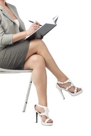 Cropped image of a sitting secretary carrying notes and pen photo
