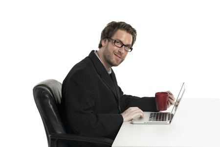 Side shot of a smiling businessman having coffee in front of his laptop Stock Photo - 17519989