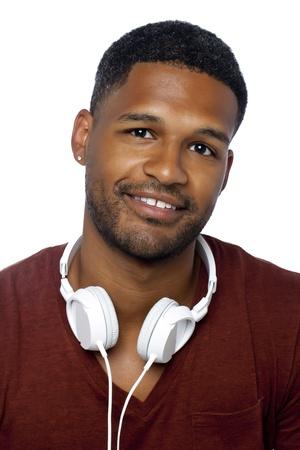 aieron: Close-up immagine di sorridente uomo scuro con le cuffie intorno al suo collo, isolato su una superficie bianca Archivio Fotografico