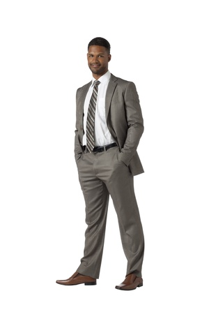 Portrait of an african american businessman standing on a white background with his hands inside his ppockets Stock Photo - 17520007