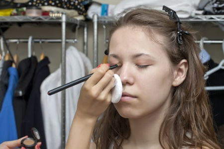 Close up image of teenage girl having her make up photo