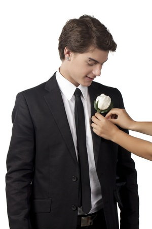 Illustration of human hand placing a white flower pin in collar of handsome teenage man illustration