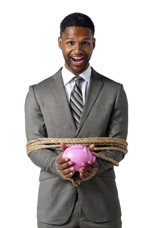 Smiling businessman tied with a rope while holding a piggy bank photo