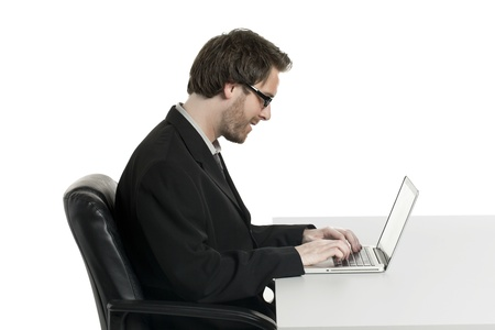 Side view shot of a smiling businessman typing on his laptop photo