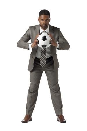 aieron: Ben vestito uomo afroamericano in possesso di un pallone da calcio in un colpo di vista frontale Archivio Fotografico