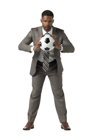 Well dressed African American man holding a soccer ball in a front view shot photo