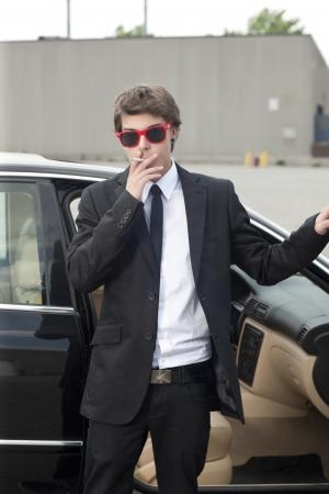 Portrait of well dressed teenage guy smoking photo