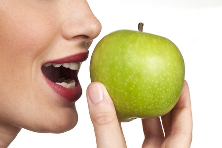 emphasised: The apple is emphasised in the closeup studio shot of a women about to bite into an fresh apple. Stock Photo