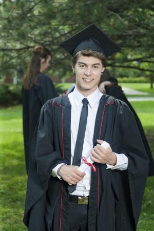 graduacion de universidad: Retrato de hombre joven guapo en traje de graduación sosteniendo su diploma