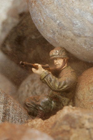 Sniper hiding in dusty rocks aiming his target photo