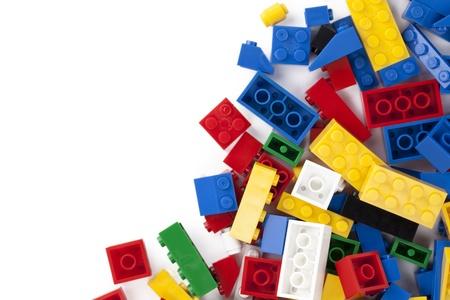 Close-up beeld van kleurrijke lego stenen verspreid op de zijkant van een witte achtergrond Stockfoto