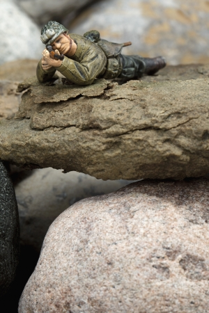 Close-up image of a sniper miniature lying on the rocks photo