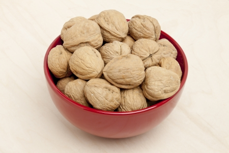 Image of a bowl full of walnuts placed on wooden table