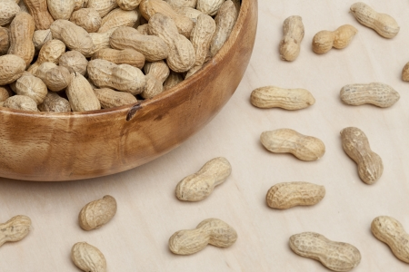 pygmy nuts: Close up image of a bowl of peanuts with scattered peanuts on the table Stock Photo
