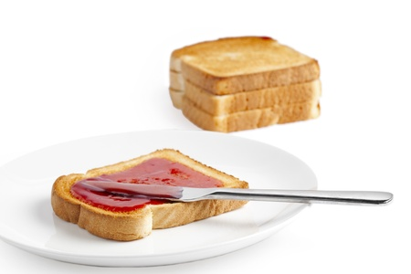 Close-up image of a bread knife spreading the strawberry jam on the bread Stock Photo - 20049753