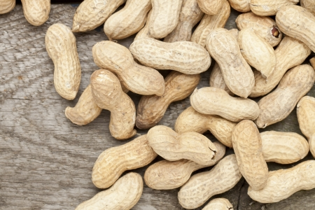 Close up image of dry organic peanuts on wooden table