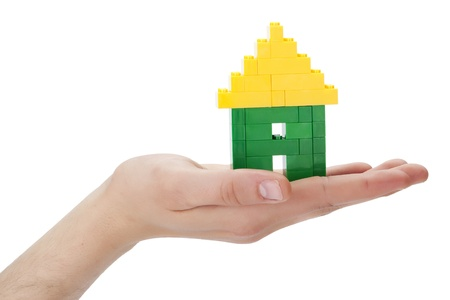 Close-up shot in the house made of lego blocks on the human's palm lifting up against the white background