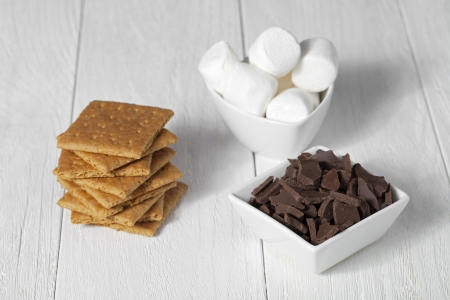 Close up image of marshmallow, crackers and chocolate on wooden table photo