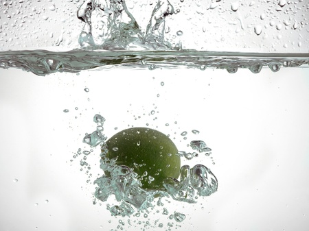 submerging: Green lime sinking water Stock Photo