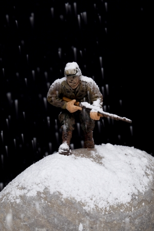 Close-up image of a brave soldier miniature fighting on the rocks under the snow rain photo