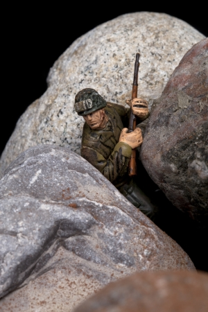 Close-up image of a toy soldier miniature holding a gun and hiding on the rocks photo