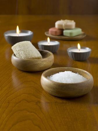 Close-up image of a spa setting with salt, soap and candles on the wooden table