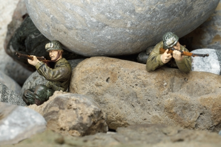 Image of two brave soldiers while holding a rifle  on the rocks photo