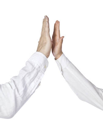 stipulation: Isolated image of two hands going to do a high five over a white background