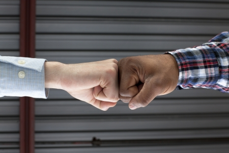 Close-up image of two human hands having a fist bump