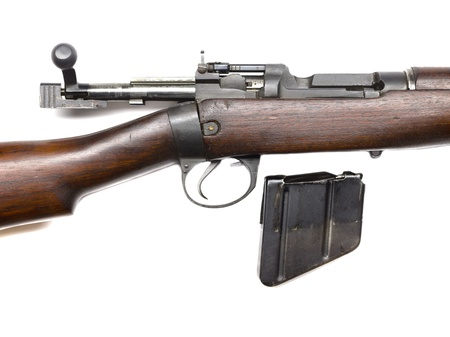 Cropped image of a vintage rifle with detached part on a white background