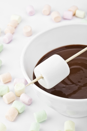 Portrait and close up image of white marshmallow on stick above the melted chocolate bowl with stray marshmallows on the side